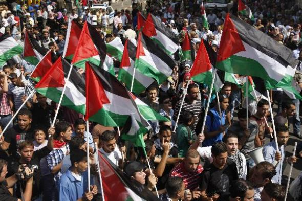 Palestinians wave flags during a rally in support of the Palestinian